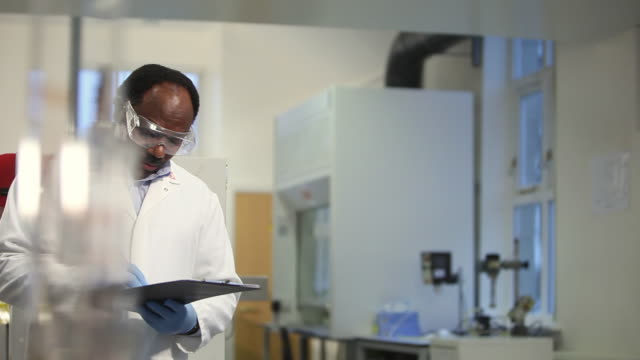 MS PAN Man writing notes in laboratory / Leeds, West Yorkshire, UK