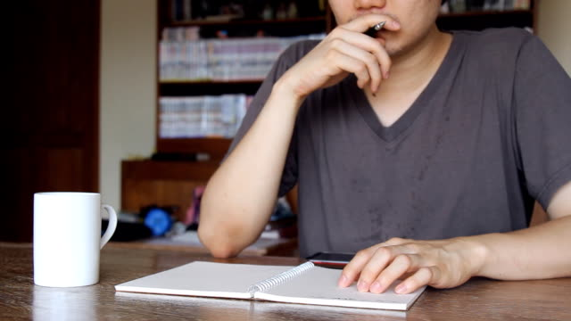 man writing on notebook and drinking coffee at home