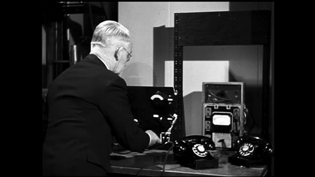 man writing something down on a notebook and nodding, then shows the notebook to another man; man testing the dials of a telephone on machine; man in... - 1940 1949 stock-videos und b-roll-filmmaterial