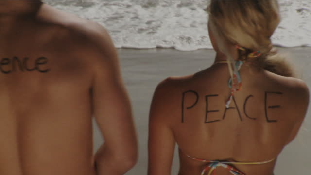 vídeos y material grabado en eventos de stock de ms ha man writing word 'peace' on woman's back standing on beach, laguna beach, california, usa - kelly mason videos