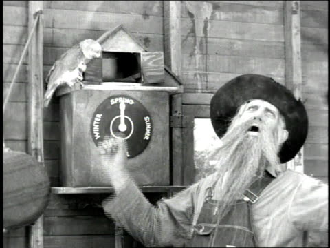 1947 ms man yawning and taking a living bird from a cuckoo clock / united states - cuckoo stock videos and b-roll footage