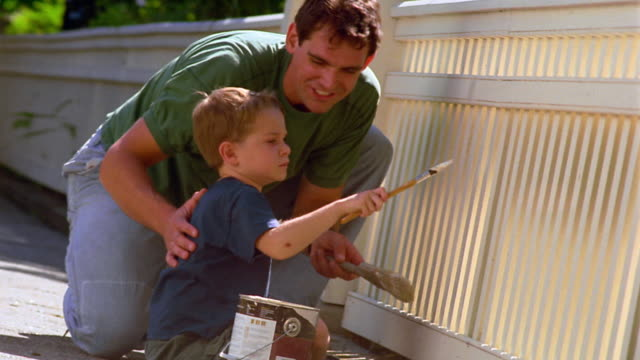 CANTED MS man + young boy painting white fence
