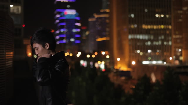 MS Man zipping up leather jacket, standing by balustrade with cityscape in background at night / Beijing, China