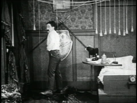 vídeos de stock, filmes e b-roll de b/w 1923 man (snub pollard) zipping up pants in bedroom / short - 1923