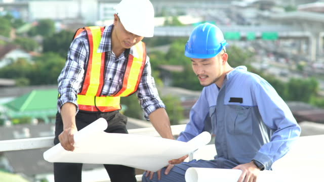 Management and Engineers meeting at terrace on top of construction site. Coworkers discussing. Boss and worker argue. Conversation in team.wear helmet hold paper plans