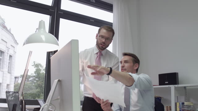 manager and employee comparing paper document and computer screen - papierkram stock-videos und b-roll-filmmaterial