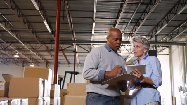MS TD Manager and male worker discussing work in warehouse / Dallas, Texas, United States