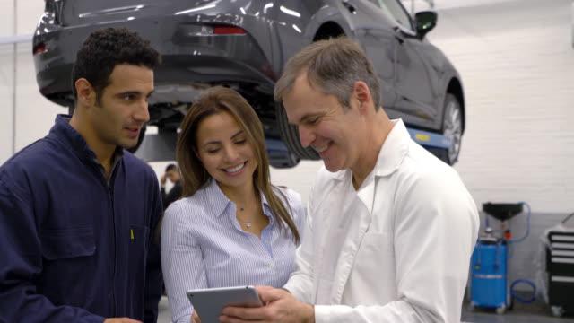 vidéos et rushes de gestionnaire et mécanicien montrant un client la liste des pièces d'auto ils ont fixé sur tablette - satisfaction