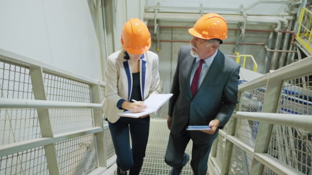 manager and quality controller moving up the stairs inside recycling facility - waste management stock videos & royalty-free footage