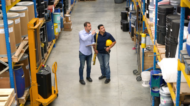 manager and worker walking between the stock of a warehouse giving instruction to worker - imbracatura di sicurezza video stock e b–roll