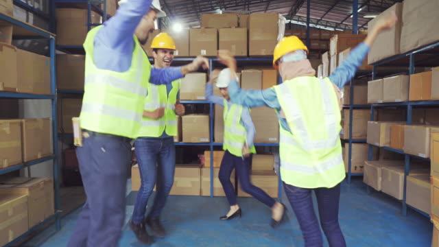 vidéos et rushes de gestionnaire et ouvriers célébrant ensemble après avoir terminé le travail dans l'entrepôt - fierté