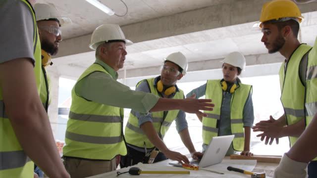 vídeos y material grabado en eventos de stock de gerente en un apretón de manos de la obra con un joven que se une a su equipo - sector de la construcción