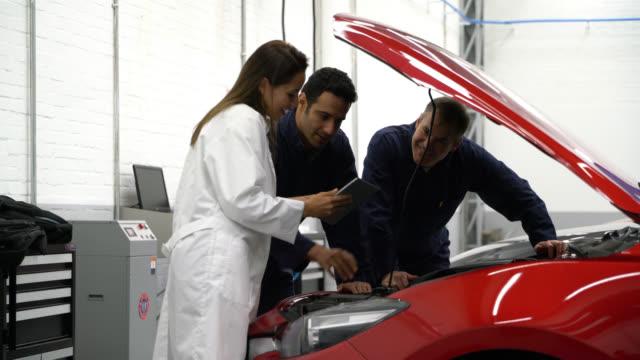 vídeos y material grabado en eventos de stock de gerente en una tienda de reparación de auto dando instrucciones a los mecánicos - garaje