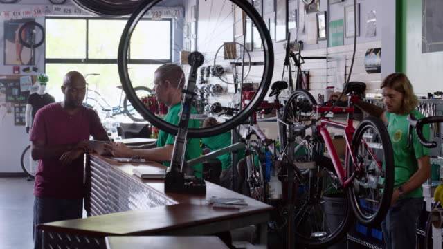 Manager chats with customer while bike mechanic works on bicycle in workshop