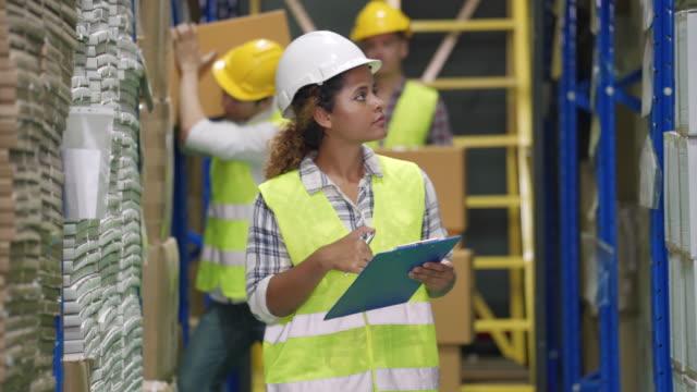 manager prüft lagerbestand und arbeiter heben waren aus dem regal im lager - box container stock-videos und b-roll-filmmaterial