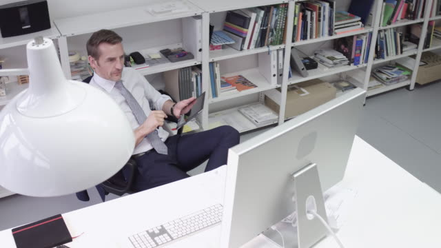 manager comparing digital tablet to computer screen