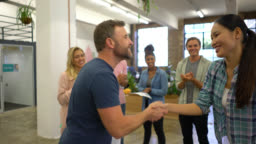 Manager congratulating a woman on her promotion and coworkers clapping all standing around her very happy