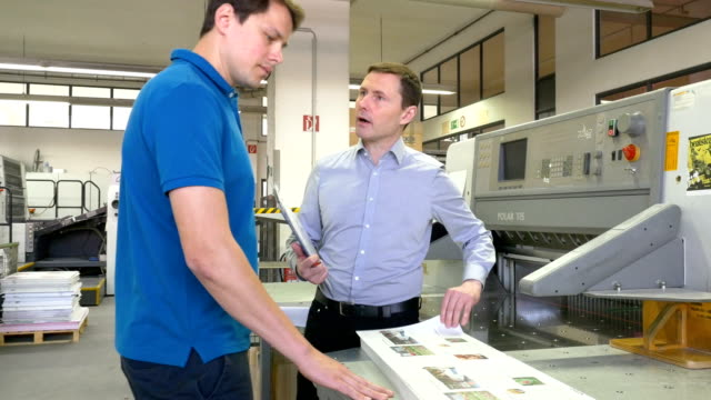 manager discussing over printout with worker - pressa da stampa video stock e b–roll