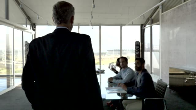 vidéos et rushes de manager discussing with team in boardroom - directeur