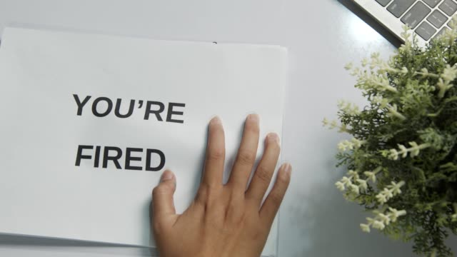 manager give notice paper you are fired to employee - table top view stock videos & royalty-free footage