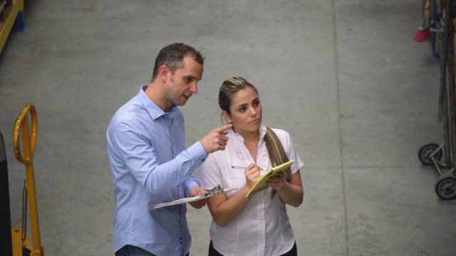 Manager of a warehouse pointing some packages to deliver giving instructions to assistant