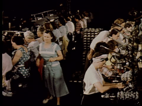 vidéos et rushes de ms, ha, manager overseeing factory workers sitting and working in rows, usa - chaîne de production
