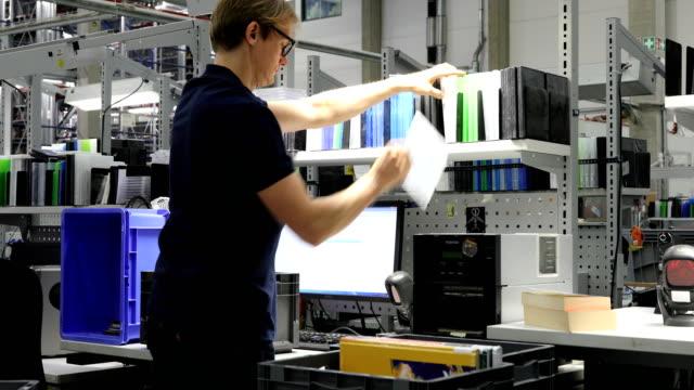 vídeos de stock e filmes b-roll de manager scanning cd cases at desk in workshop - one mid adult man only