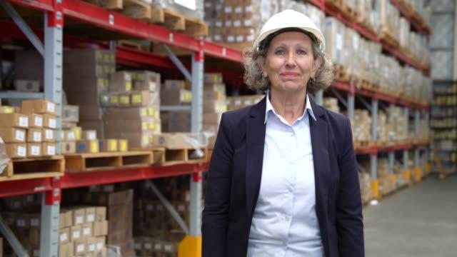 マネージャー笑顔と倉庫で腕を交差 - ワーキングシニア点の映像素材/bロール