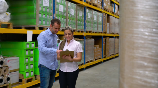 Manager talking to his assistant at a warehouse pointing to some packages