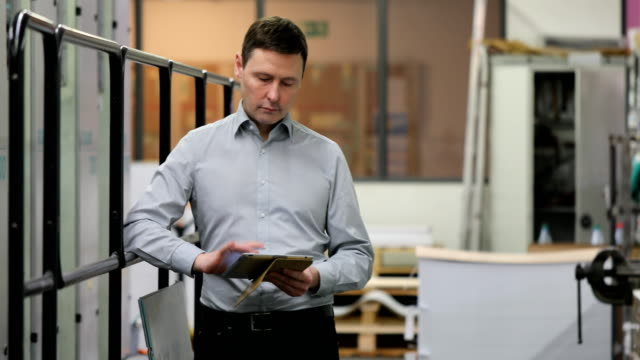 Manager using digital tablet at printing plant