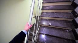 manager walks up stairs to door on landing view from headcam