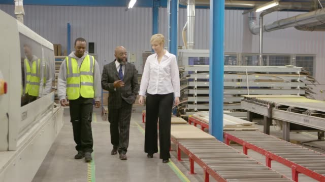 manager with colleagues on factory shop floor - manufacturing occupation stock videos & royalty-free footage