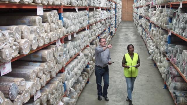 manager mit arbeitnehmerin blick auf teppiche im lager - teppich stock-videos und b-roll-filmmaterial