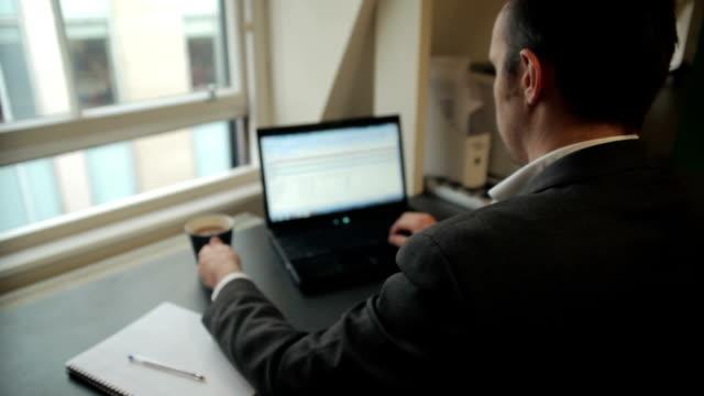 vídeos y material grabado en eventos de stock de gerente trabajando en un portátil bebiendo café junto a la ventana - dispositivo de entrada