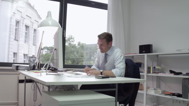 manager writing and cheering at his desk