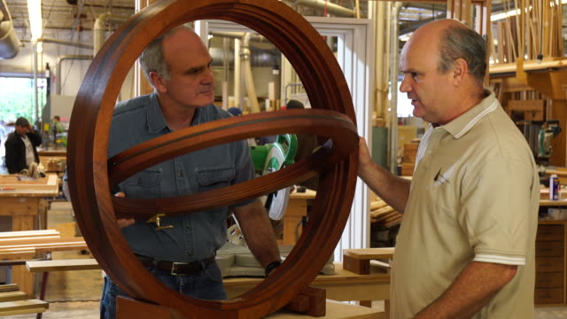 managers of woodworking shop examine custom, circular window frame - window frame stock videos and b-roll footage