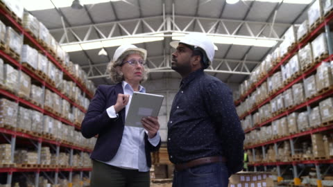 managers with tablet pc discussing in warehouse - quality control stock videos & royalty-free footage
