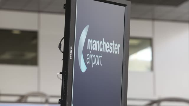 a manchester airport sign is seen on an electronic information board near checkin desks in the departures terminal of manchester airport in... - plc stock videos & royalty-free footage