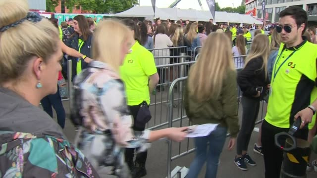 Ariana Grande headlines One Love Manchester concert to benefit victims Various shots people along and armed police nearby Concert goers through...