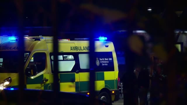 Hospitals still treating 59 injured by bomb NIGHT Ambulance with lights flashing People around open door of ambulance