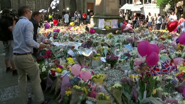 Minute's silence in St Ann's Square ENGLAND Manchester St Ann's Square EXT Floral tributes in sqaure / Clock countdown to 11am / Minute silence...