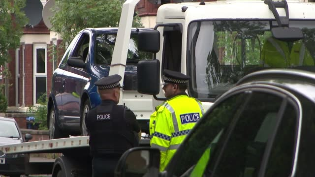 police arrest a 25 year old man old trafford police officers loading arrested man's car onto truck in suburban street - itv weekend evening news stock-videos und b-roll-filmmaterial