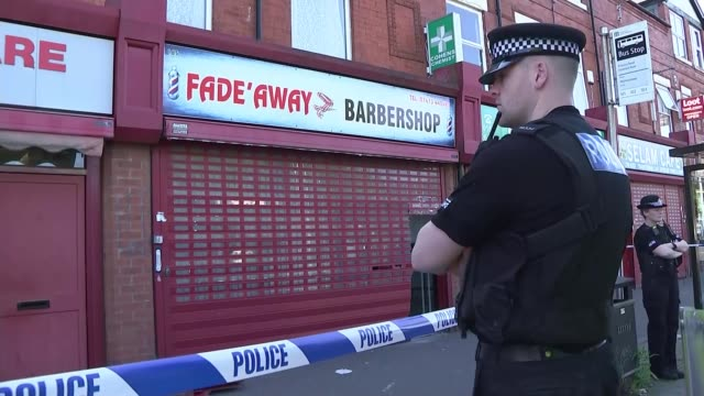 Police investigation continues ENGLAND Manchester Moss side EXT Police officer standing by cordon tape outside 'fade Away Barbershop' and 'Pharmacy'...