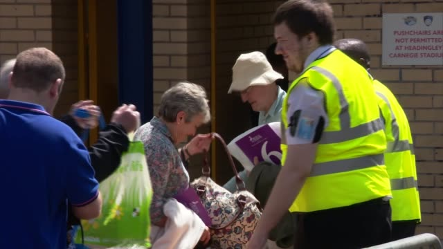 Security stepped up across UK West Yorkshire Leeds Headingley Stadium Various shots people having bags checked by security Armed police towards Close...