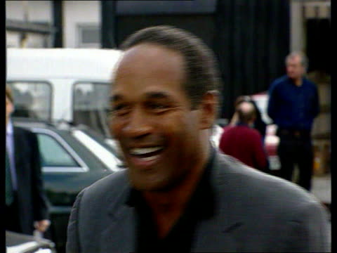 october; lib england: manchester: oj simpson laughing and chatting during visit to uk - o・j・シンプソン点の映像素材/bロール