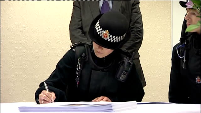 tributes to pcs nicola hughes and fiona bone police officers sitting at table and signing book of condolence / man signing book union jack flag... - book signing stock videos & royalty-free footage