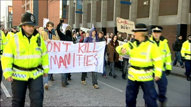 Protesters marching along with banner reading 'Don't Kill Humanities' as escorted by police officers
