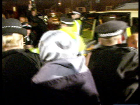stockvideo's en b-roll-footage met manchester: rusholme: ext/night somalian men and women outside house to police officers at front door of neighbouring house police officers and local... - adn