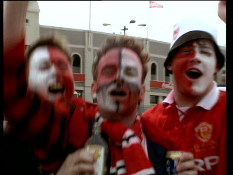 Manchester United fans with faces painted sing and chant to camera England