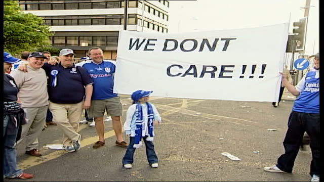 manchester united win fa cup final; itn wales: cardiff: ext millwall fans holding up 'we don't care!!!' banner vox pops - itv weekend late news点の映像素材/bロール